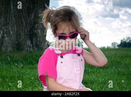Child wearing sunglasses with bad attitude - Stock Photo