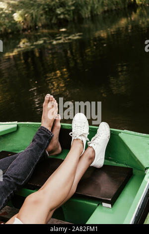 cropped view of barefoot man and girl in sneakers relaxing in boat on lake - Stock Photo