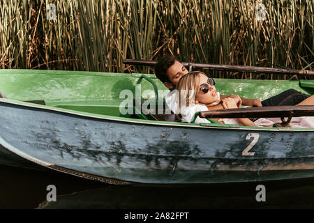 young couple relaxing in boat on river near thicket of sedge - Stock Photo
