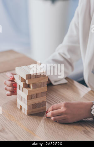 cropped view of risk manager taking wooden block out of stack