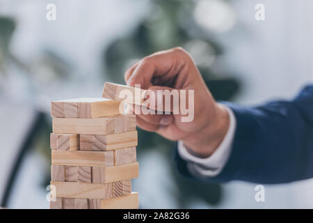cropped view of businessman putting wooden block on stack