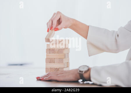 cropped view of businesswoman putting wooden block on stack