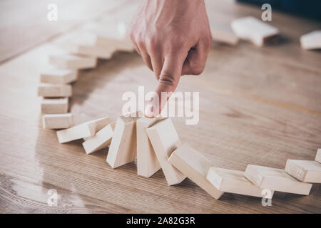 cropped view of businessman stopping domino effect of falling wooden blocks