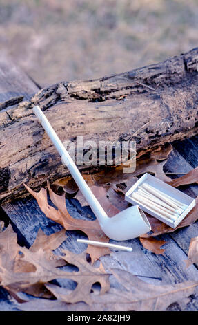 clay pipe with matches on a rustic back drop Stock Photo