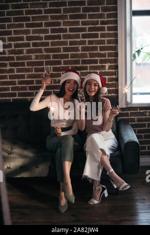 two young, happy businesswoman in santa hats smiling at camera while sitting on sofa with sparklers and champagne glasses - Stock Photo