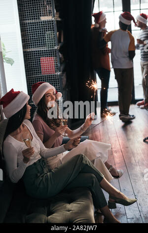 attractive, cheerful businesswoman in santa hats sitting on sofa with sparklers and champagne glasses - Stock Photo