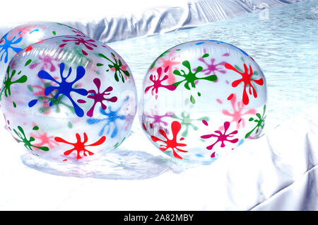 colorful inflatable beach balls on a small water filled pool - Stock Photo