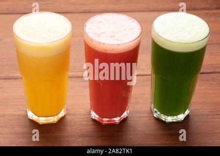 Array of colorful fresh fruit juices served in tall glasses on a wooden background - Stock Photo