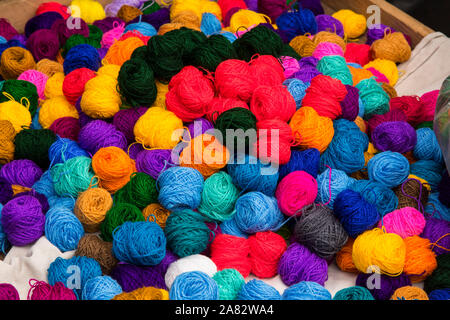 Balls of yarn for sale for weaving the traditional huipils and tzute utility cloths in the Chichicastenango, Guatemala market. - Stock Photo