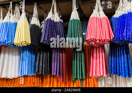 Bundles of colorful candles for Catholic and Mayan religious ceremonies  hang by their wicks, for sale in the market in Santiago Atitlan, Guatemala. - Stock Photo