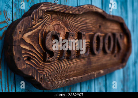 wooden sign with the word Salon, blue boards in the background, vintage style - Stock Photo