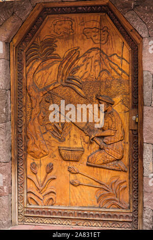 Carved wooden door depicting a woman in traditional dress including a tocoyal weaving on a back loom.  Santiago Atitlan, Guatemala. - Stock Photo