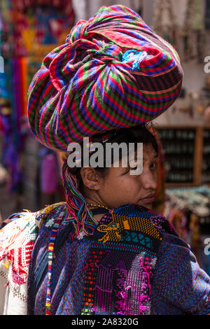 Young woman from Sang Antonio Palopo at the market in Chichicastenango, Guatemala carrying her goods on her head, looking back over her shoulder.  She