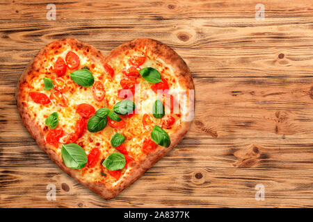 Tasty heart-shaped pizza on wooden background - Stock Photo