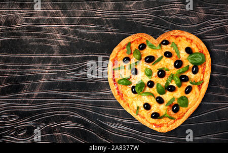 Tasty heart-shaped pizza with olives on wooden background - Stock Photo