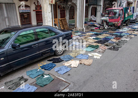 PENANG, MALAYSIA, NOV 12 2017, Short pants lying on the asphalt road. Drying clothes on the street of the city. - Stock Photo