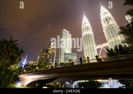 KL Tower and the Petronas Twin Tower illuminated at dusk. People enjoying the view from a bridge in KLCC Park