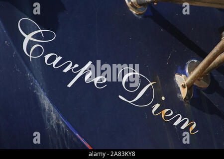 Latin words carpe diem translated as meaning 'seize the day'. The name of a boat seen in dry dock in the port of Numana on the Adriatic coast in Italy - Stock Photo