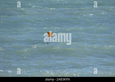 marker flag for a clam or mussel fishing pot in the Adriatic sea near Ancona in Italy in early spring - Stock Photo