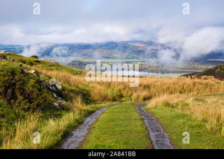 Farm track in Rhinog hills above Afon Dwyryd river estuary with low cloud on mountains of northern Snowdonia. Eisingrug Harlech Gwynedd Wales UK - Stock Photo