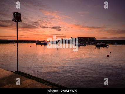 Lyme Regis, Dorset, UK. 6th November 2019. UK Weather: Beautiful sunrise at the historic Cobb Harbour at the coastal resort town of Lyme Regis.  The sky over the Cobb glows with soft pink hues on a chilly morning ahead of unsettled conditions forecast later. Credit: Celia McMahon/Alamy Live News. - Stock Photo