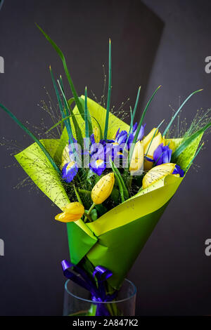 Yellow tulips and violet irises, bouquet of flowers in a bright wrapper in a glass vase. Greeting card for all occasions, especially spring. Romantic - Stock Photo