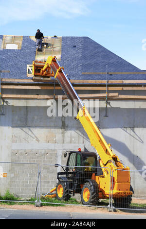 Roofer using a telescopic crane to access the site. - Stock Photo