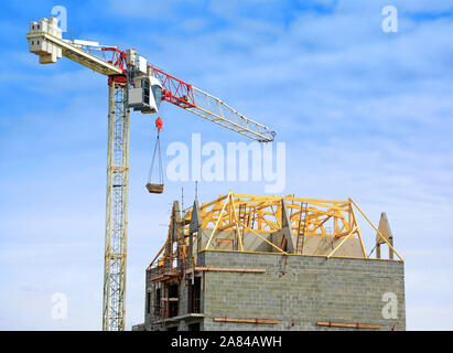 Use of a crane for the construction of the roof of a house. - Stock Photo