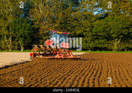 A tractor pulls a plough and press cultivator across a field in autumn ready for seeding. - Stock Photo