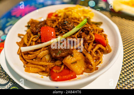 Traditional Mouthwatering Central Asian Uyghur Fried Noodles Lagman Dish with Vegetables on a White Plate - Stock Photo