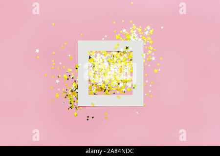 Creative layout with white frame and little silver and golden stars on pink background. - Stock Photo
