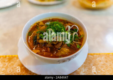 Traditional Mouthwatering Central Asian Uyghur Lagman Soup Dish with Vegetables on a White Plate - Stock Photo