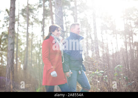 Couple hiking in sunny, autumn woods