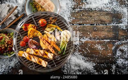 Assorted farm fresh vegetables grilling on a BBQ outdoors in winter snow with halloumi or bean curd kebabs for a healthy vegetarian diet - Stock Photo