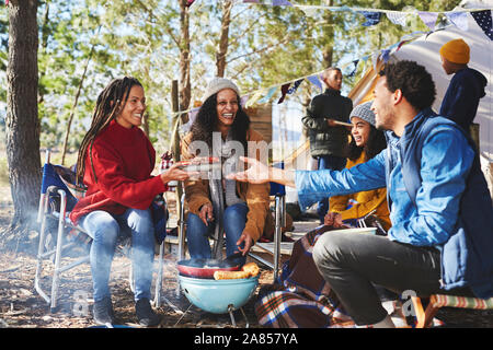 Happy family eating at sunny campsite - Stock Photo