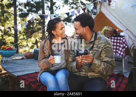 Affectionate young couple with binoculars drinking coffee at campsite - Stock Photo