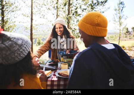 Happy mother and kids eating at campsite - Stock Photo