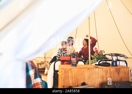 Happy family relaxing in camping yurt - Stock Photo