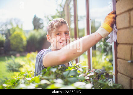 Portrait smiling, confident male worker installing windows on house - Stock Photo