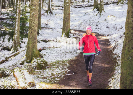 Woman jogging on trail in snowy woods - Stock Photo