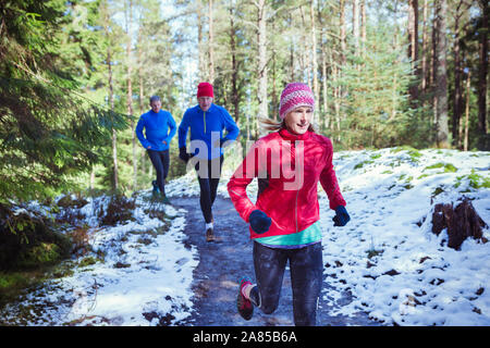 Family jogging on trail in snowy woods