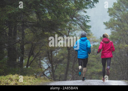 Couple jogging on trail in rainy woods - Stock Photo