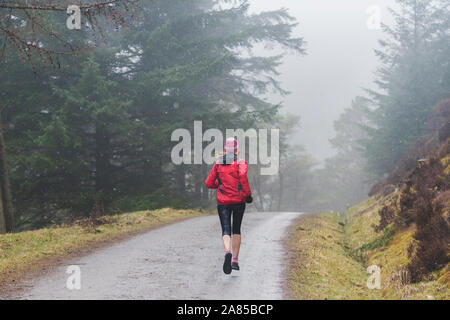 Woman jogging on trail in rainy woods - Stock Photo