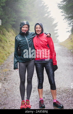Portrait happy mother and daughter hiking on trail in rainy woods - Stock Photo