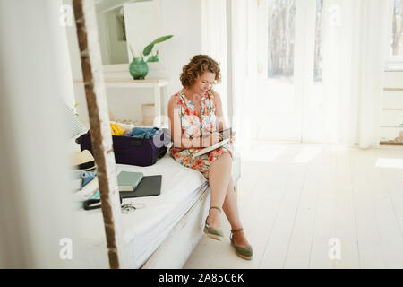 Woman writing in journal next to suitcase on beach hut bedroom - Stock Photo