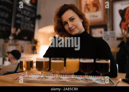Redhead woman does a degustation of a variety of light and dark czech beer in a bar pub - Stock Photo