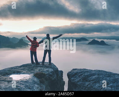 Lovers mirroring in water eye at mountain summit above thick mist.  Climbing couple at top of summit with amazing aerial view - Stock Photo