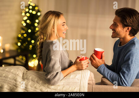 Cozy winter holidays. Loving couple drinking hot chocolate - Stock Photo