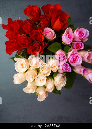 Bunch of opened roses of different colors on grey concrete table - Stock Photo