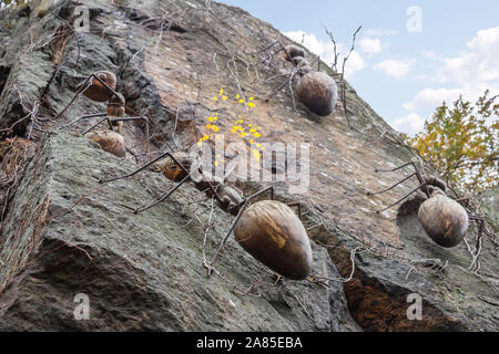 KOTKA, FINLAND - NOVEMBER 02, 2019: Figures of ants made of wood and metal on a steep rock in one of the city parks of Kotka. - Stock Photo
